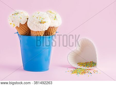 Ice Cream Cones In A Blue Bucket And Small White Plate In Forma A Heart With Topping On A Pink Backg