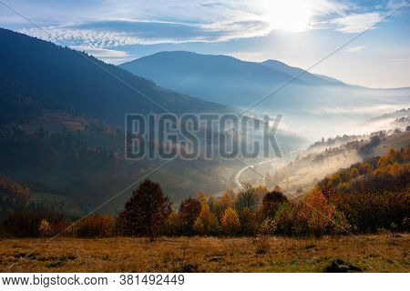 Misty Autumn Morning In Carpathian Mountains. Valley Full Of Fog. Sunny And Hazy Weather With Clouds
