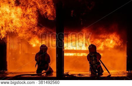 Firefighters using water fog fire extinguisher to fighting with the fire flame in large building. Firefighter and industrial safety disaster and public service concept.