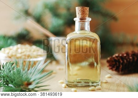 Cedar Products: Cedar Pine Nuts Oil In Glass Bottle, Pine Nuts, Cones, Brunches On A Wooden Broun Ba