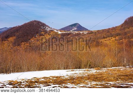 Springtime In Mountain Landscape. Leafless Birch Trees And Snow On The Meadow. Ridge In The Distance