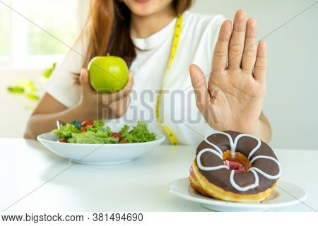 Diet Concept. Healthy Women Use Hands To Reject Unhealthy Foods Such As Donuts Or Desserts. Slim Wom