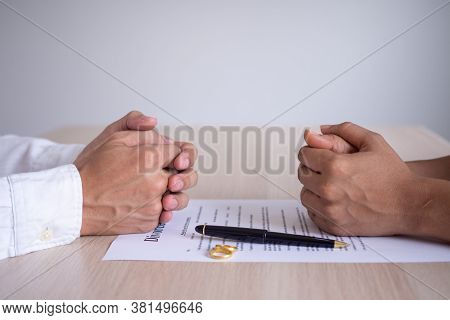 The Hands Of The Wife And Husband Rests On The Divorce Documents. Filing Divorce Documents Or Prenup