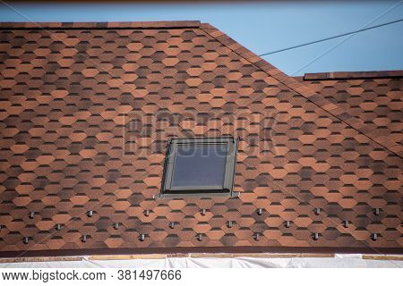 Roof With Mansard Windows And Shingles. Skylight On A Roof Shingles Under Construction