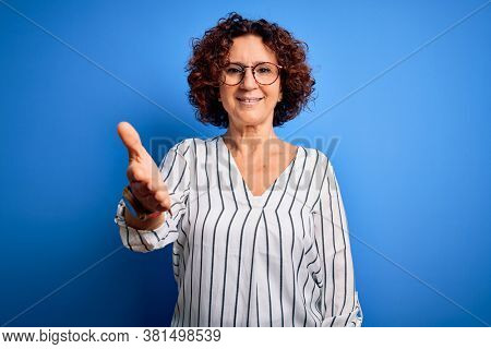Middle age beautiful curly hair woman wearing casual striped shirt over isolated background smiling friendly offering handshake as greeting and welcoming. Successful business.