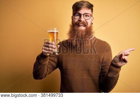 Irish redhead man with beard drinking a glass of refreshing beer over yellow background very happy pointing with hand and finger to the side