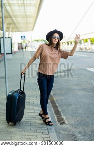 Young Woman Calling Taxi, Arriving At Airport Travelling Alone