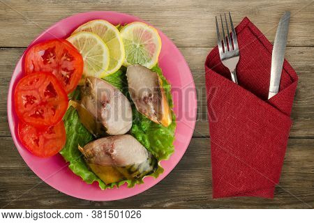 Smoked Mackerel On A Pink Plate With Fork And Knife Top View. Mackerel With Lemon And Tomato On Brow