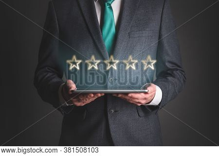 Five Stars Service Rating Concept. Businessman With A Digital Tablet In Hands With A 5 Golden Stars