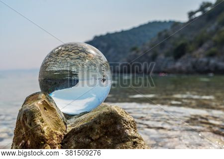 Crystal ball on stones near the sea. Original upside down view and rounded perspective of the sky and pebble seabed. Original and engaging picture.