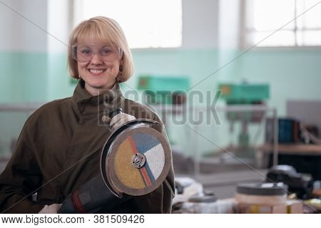 Happy Woman Worker With A Angle Grinder In Hands Close Up.