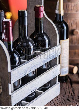 Wine bottles in wooden crate and oak wine keg.