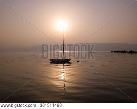 Sunrise Over The Lake. Boat Floating On The Calm Water Under Amazing Sunset.