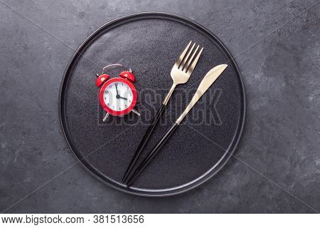 Red Alarm Clock, Fork, Knife And Empty Black Ceramic Plate On Dark Stone Background. Intermittent Fa