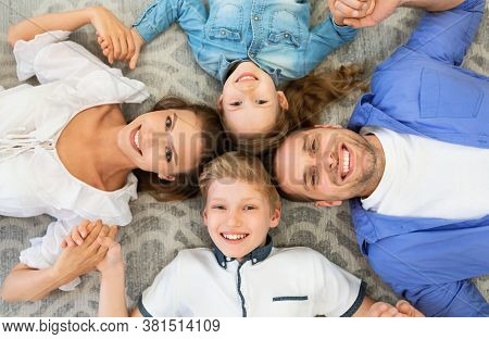 Family Bond. Happy Parents And Kids Lying Holding Hands Smiling To Camera Posing On Floor Indoors. A