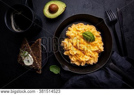 Fresh Cooked Scrambled Eggs In A Cast Iron Skillet On Black Background, Top View