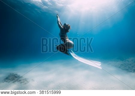 Attractive Woman Freediver Glides And Posing Over Sandy Bottom With White Fins.