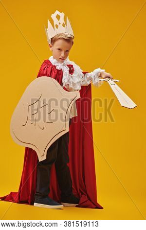 Full length portrait of a cute brave boy in a knight costume with cardboard armour. Yellow background. Childhood dreams and fantasy. Carnival, Theater.