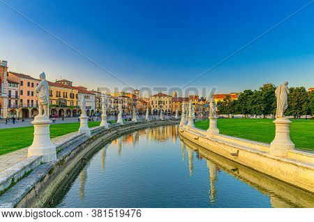 Padua Cityscape With Statues Near Small Canal On Piazza Prato Della Valle Square And Row Of Colorful