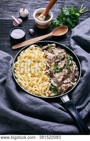 Beef Stroganoff Cooked With Sour Cream Mushrooms Sauce, Served With Egg Noodles In A Skillet On A Da