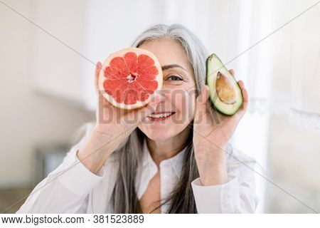 Close Up Portrait Of Senior Gray Haired Woman In The Kitchen, Holding Fresh Avocado And Grapefruit P