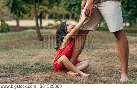 Cheerful Smiling Daughter With His Father Swinging On Daddy's Leg Outdoors.