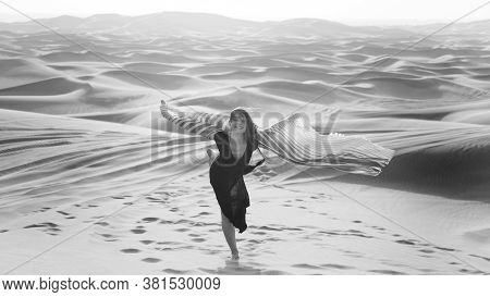 Young Woman Happily Smiling Dancing With A White Wide Shawl In Her Hands. Black And White Shot