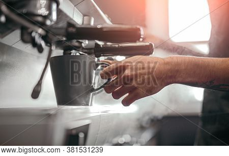 Side View Of Crop Anonymous Male Bartender Pouring Hot Coffee From Steamy Coffee Machine Into Cup Wh
