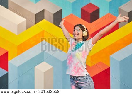 Excited Young Female Hipster In Headphones Raising Arms And Smiling While Listening To Music During