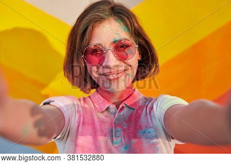 Delighted Woman In Stylish Sunglasses And With Paint On Face And T Shirt Smiling And Taking Selfie A