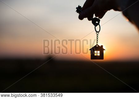 Silhouette Of A House Figure With A Key, A Pen With A Keychain On The Background Of The Sunset. They