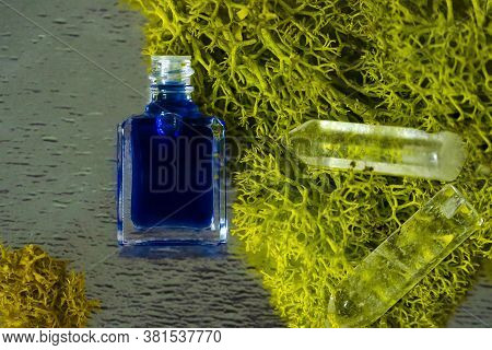 A Bottle Of Aurasoma With The Blue Essence And Crystal On The Moss Background.