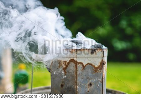Burning Coal In A Rusty Metal Heater In The Summer. Smoke Coiming From A Coal Heater In A Garden. He