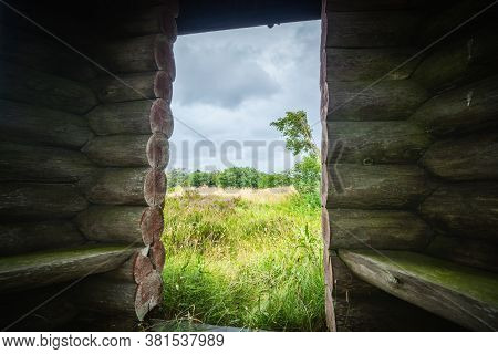 Small Shelter Made Of Wooden Logs In The Wilderness. Wooden Hut In The Wild Nature On A Cloudy Day.