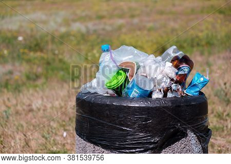 Kryvyi Rih, Ukraine - August, 2020.  Plastic Bottles And Bags In Overloaded Garbage Bin On A Grass A