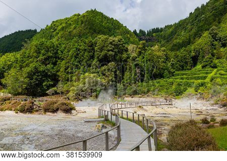 Furnas: the steam from Hot springs and fumaroles at the edge of lagoa das Furnas, volcanic calderas at Furnas Lake