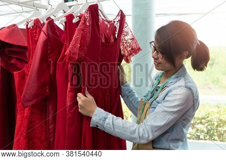 Happy Young Asian Woman Dressmaker Fashion Designer Is Checking For Completion For A Suit And Dress