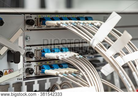Fiber Optic Cables With A Kink Protection Metal Braid With White Tags Are Connected To The Device. H