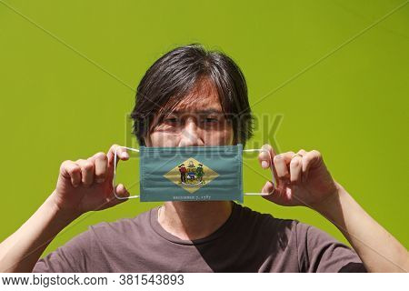 A Man And Hygienic Mask With Delaware Flag Pattern In His Hand And Raises It To Cover His Face. A Ma