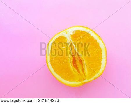 Bright Juicy Orange On A Pink Background. A Vagina Symbol. The Concept Of Sex. Womens Personal Hygie