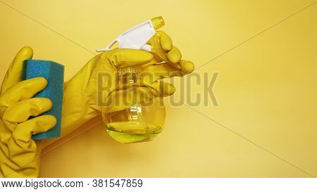 Hand In A Rubber Glove Holds A Cleaning Sponge On A Yellow Background. Cleaning Concept, Cleaning Se