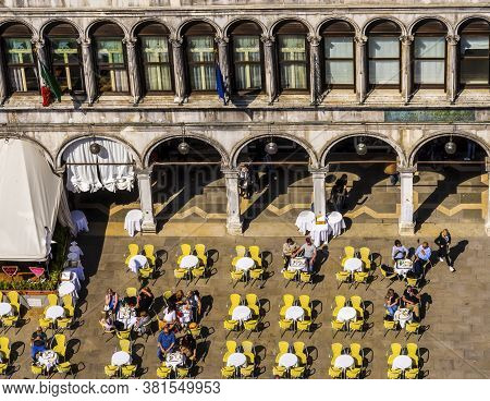 Venice, Italy - April 22, 2019 Tourists Eating Outside In Piazza San Marco Saint Mark's Square In Ve
