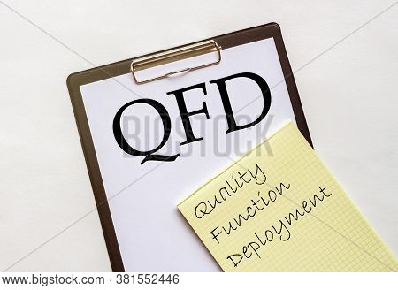 White And Yellow Paper With Text Qfd Quality Function Deployment On A White Background With Statione