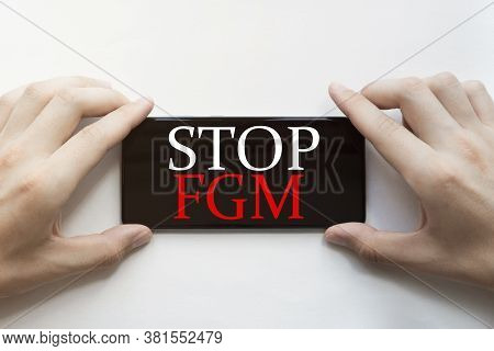 Male Hands Are Holding Black Phone With Text Stop Fgm On White Background