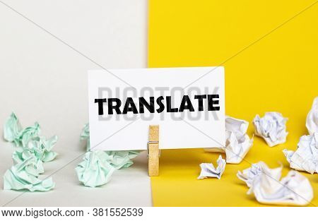 White Paper With Text Translate On A Clothespin On Yellow And White Backgrounds With Paper Wads Of D