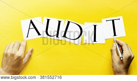 White Paper With Text Audit On A Yellow Background With Man's Hands