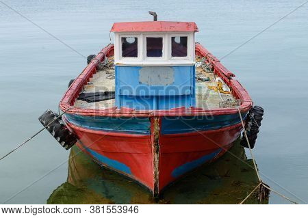 Old Red Wooden Fishing Boat Anchored At Sea