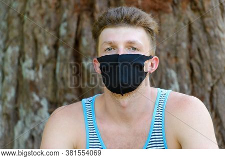 Young Man With Black Medical Mask On Wood Background