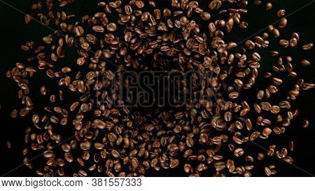 Fresh roasted coffee beans flying in the air, isolated on black background