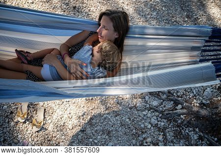 Top View Of Young Mother And Her Toddler Daughter Cuddling And Resting In A Hammock In The Shade On